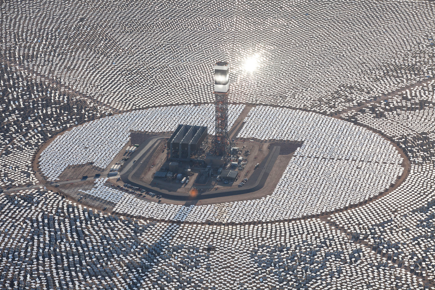 IVANPAH, CALIFORNIA, APRIL 05 2013: The top of Tower 1's is {quote}lit{quote} as a steam blow test is in progress in this aerial view of Tower 1 and its heliostats at the Ivanpah Solar Power Facility. Located in the Mojave Desert 40 miles southwest of Las Vegas, The Ivanpah Solar Power Facility is a solar thermal power project, currently under construction, with a planned capacity of 392 megawatts, enough to power approximately 140,000 houses. It will deploy 170,000 heliostat mirrors spread over 4,000 hectares, focusing solar energy on boilers located atop three solar power towers, generating steam to drive specially adapted steam turbines The project, developed by Bechtel, will cost $2.2 billion and be the largest solar farm in the world (photo Gilles Mingasson/Getty Images for Bechtel).