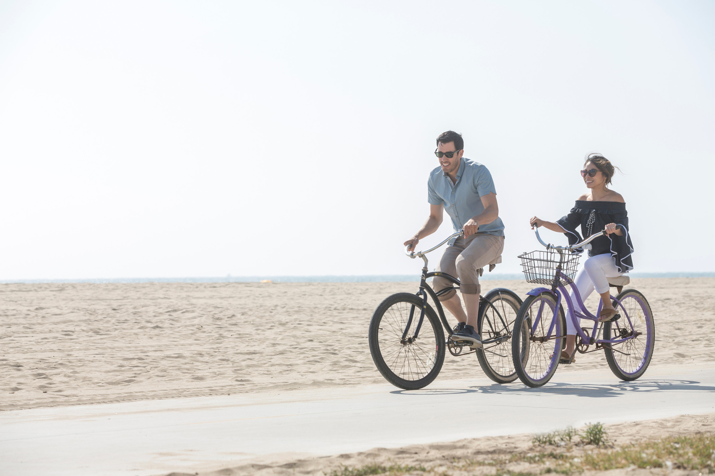 Host Drew Scott and fiancee Linda Phan enjoy a bike ride on the Venice Beach boardwalk, as seen on Property Brothers at Home: Drew's Honeymoon House.