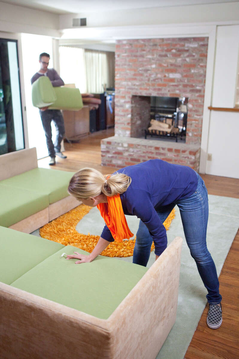Host Casey Noble and co-host Joel West bring in the refurbished sofa pillows for Erin Gardner and Thomas Steffan's living room before the reveal. In the Steffan family since it was built in 1954, the mid-century modern house or its furniture have never been updated, and host Casey Noble plans on brightening the walls with a warm white paint, re-finishing the sofa and chair, adding custom plywood-walnut shelves and tv dresser, and a shag rug to transform the dark, drab living room into a bright, hip and fun room more reflective of Erin and Thomas' personalities.