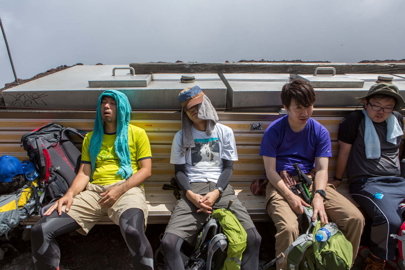 Exhausted hikers rest at a station on the Yoshida trail, Mount Fuji's most popular route.