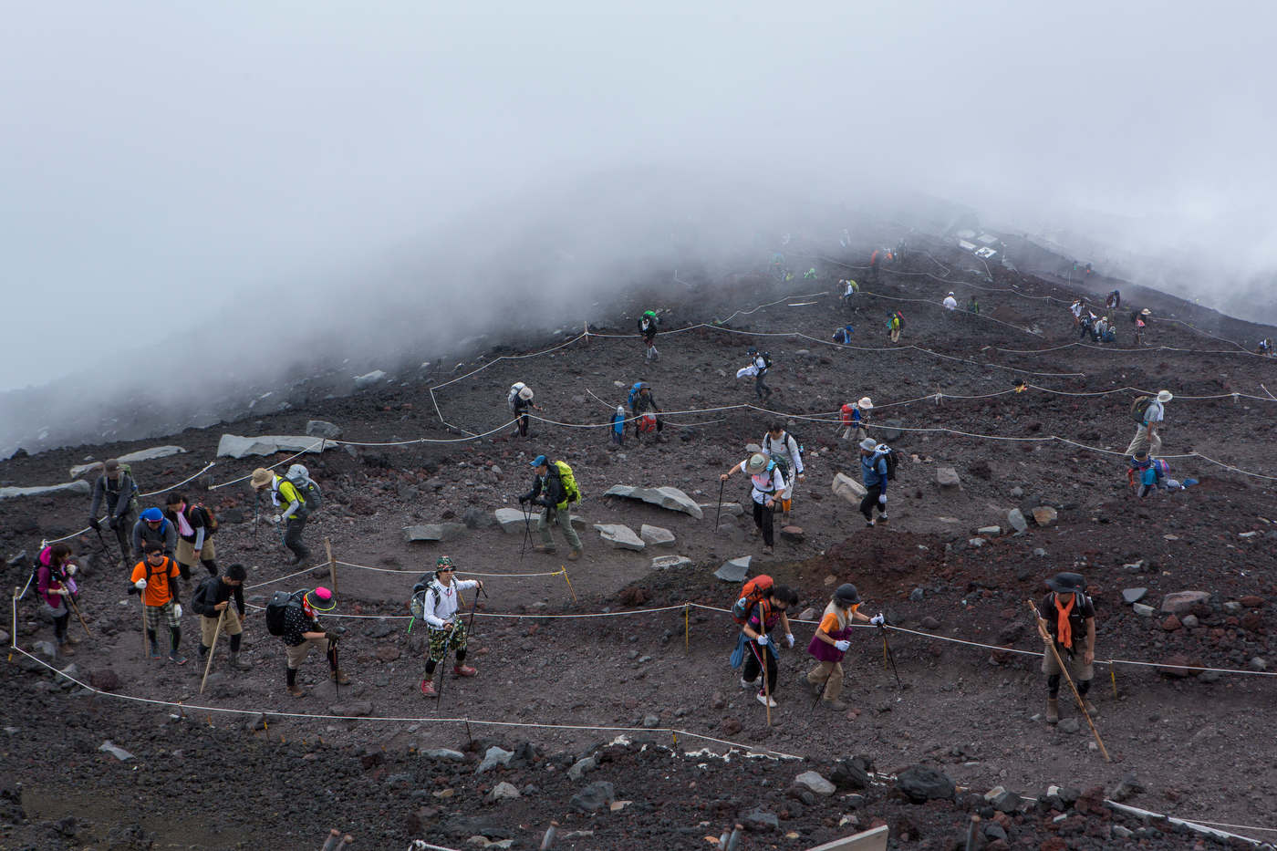 Surrounded by rolling clouds, hikers walk up on the Yoshida trail, a Mount Fuji's most popular route.