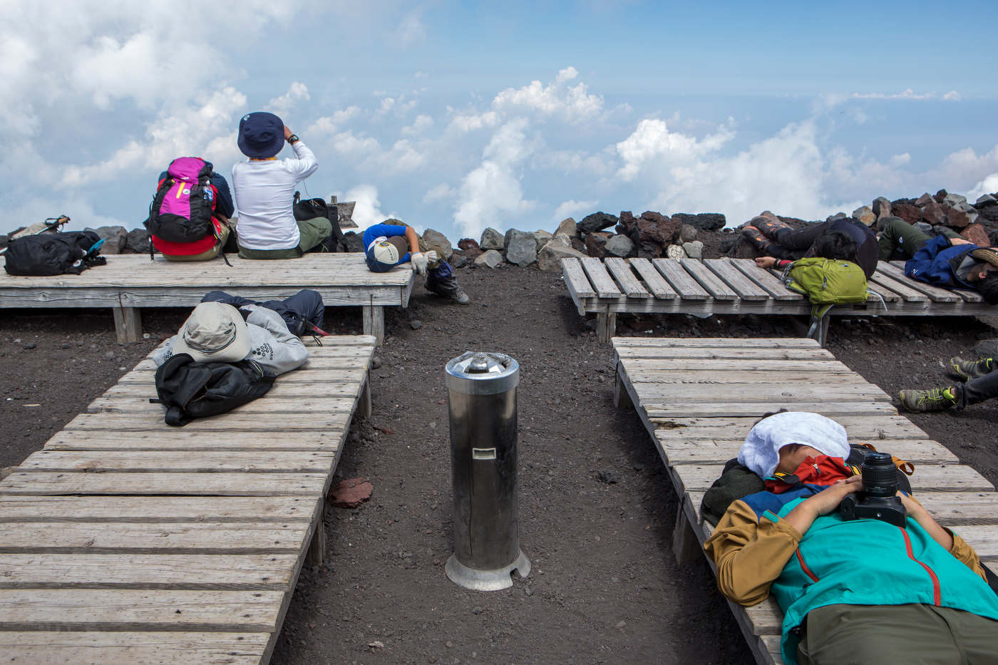 Exhausted hikers rest on wooden benches after reaching Mount Fuji's 13,389 ft summit.