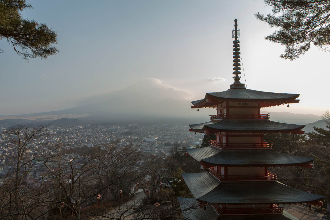 Clouds wrap the summit of Mt. Fuji at sunset behind the Chureito Pagoda.