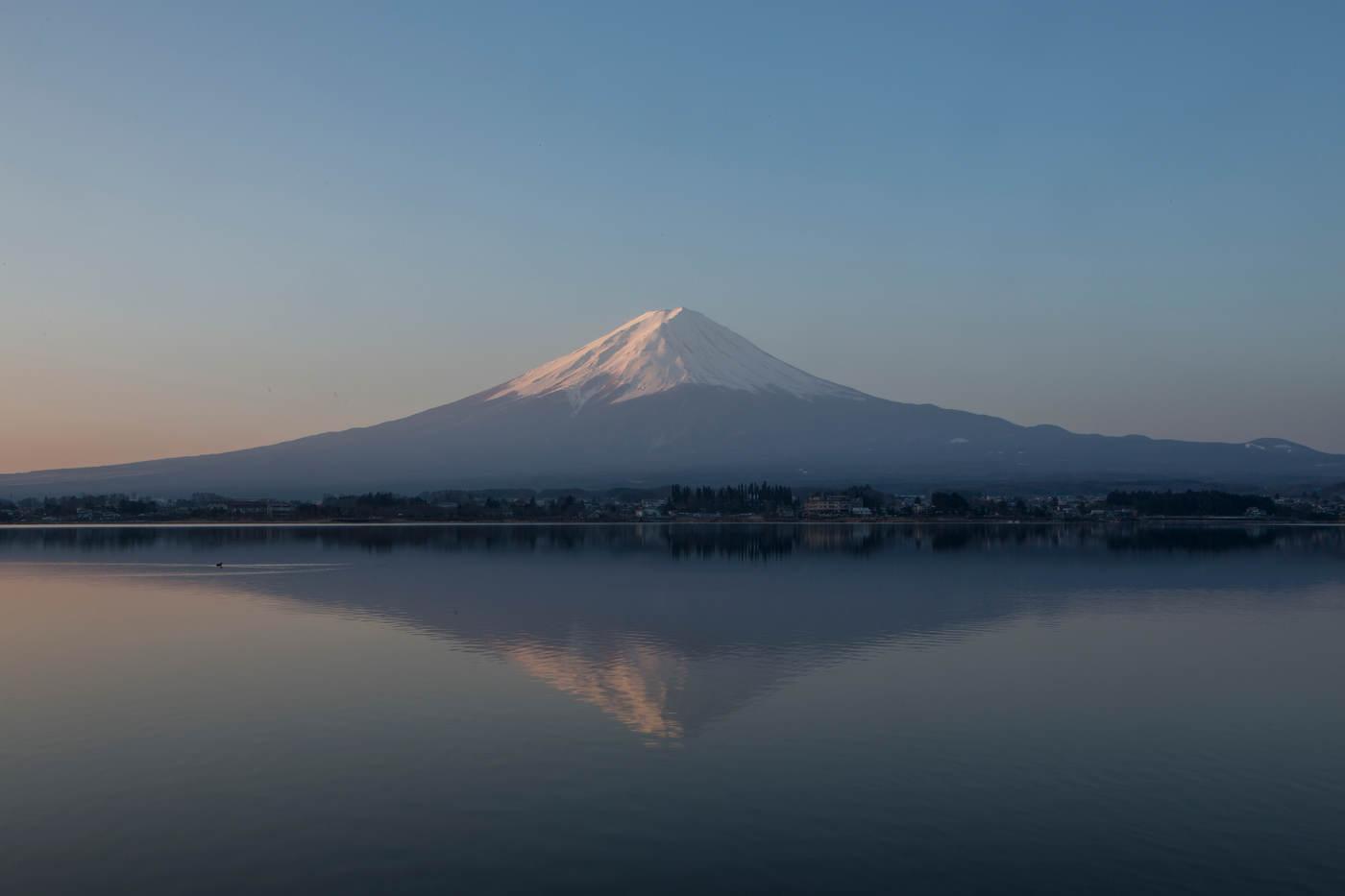Mt. Fuji reflects in the waters of Lake Kawaguchiko at sunrise.