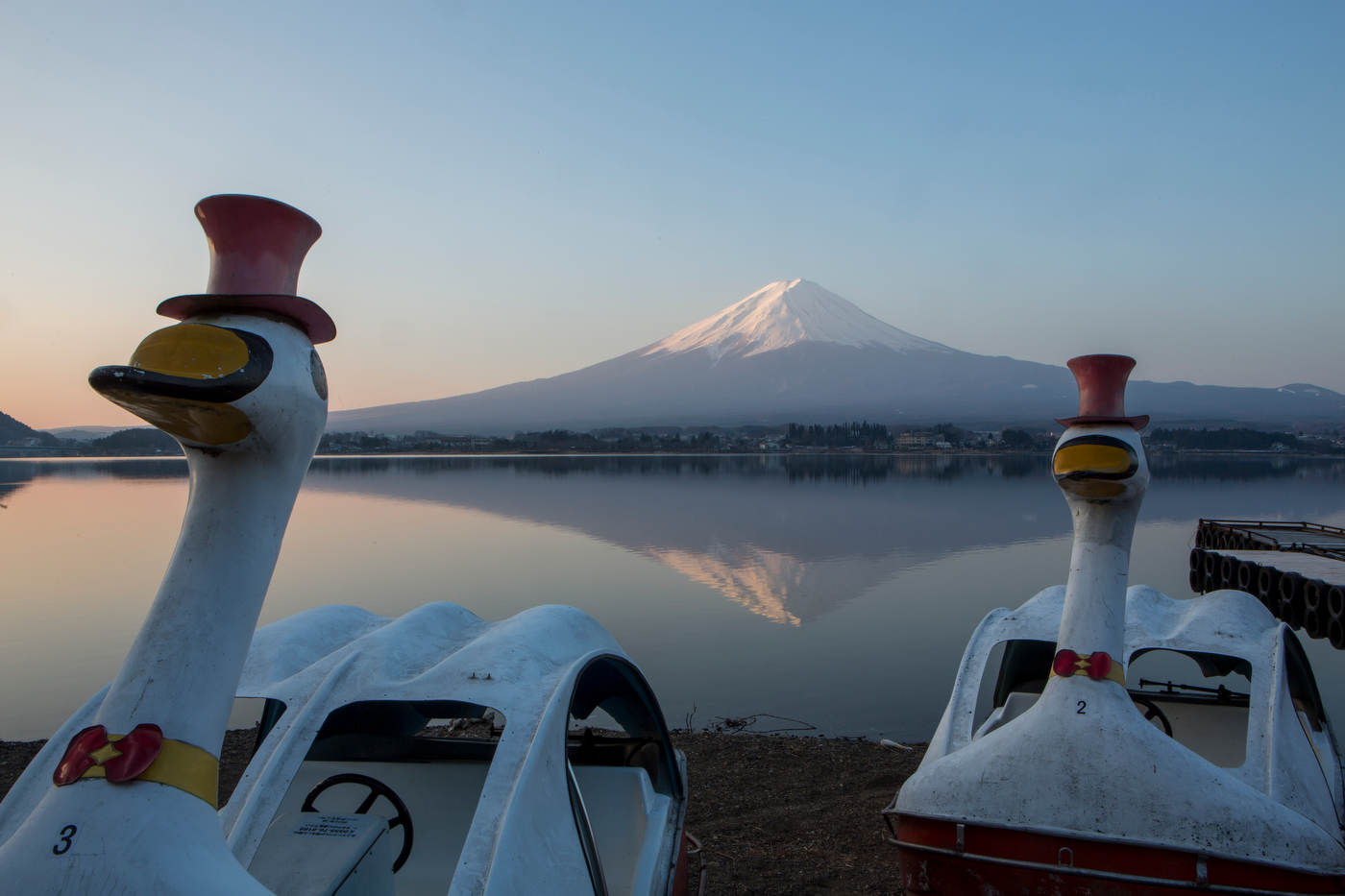 Framed by rental pedal boats, Mt. Fuji reflects in the waters of Lake Kawaguchiko at sunrise.