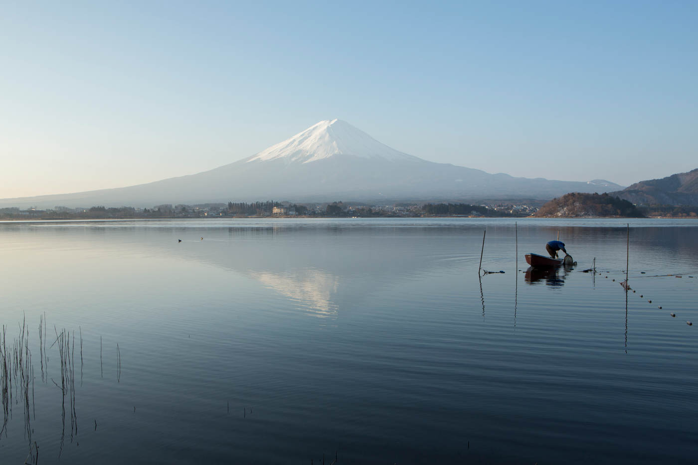 A local fisherman plies the waters of Lake Kawaguchiko, with Mt. Fuji as a backdrop.