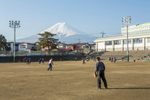 Retirees play baseball with Mt. Fuji as a backdrop.