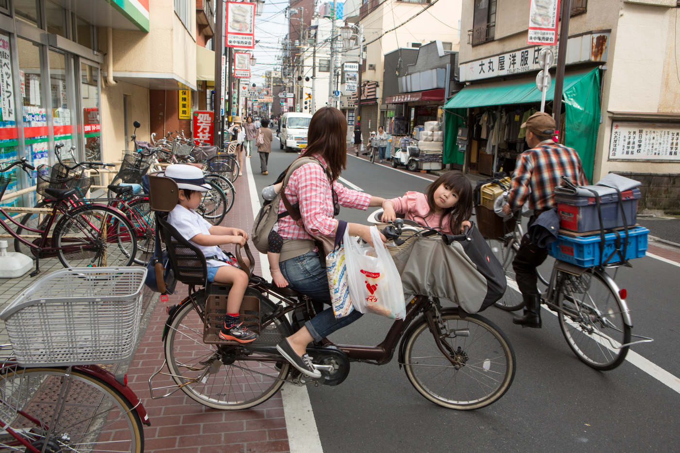 Woman on a bicycle with her three kids, Sugamo.