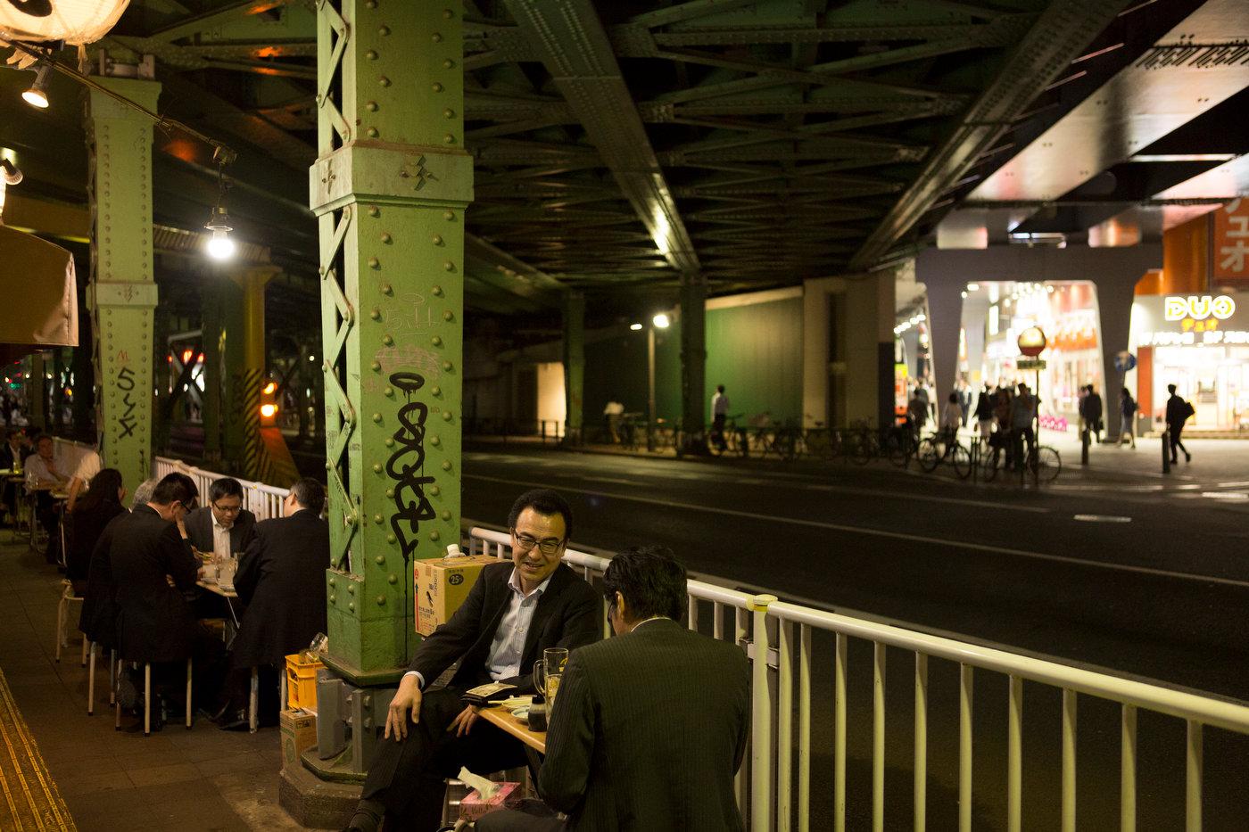 Salarymen enjoy an evening drink under the train tracks near Yurakucho Station.