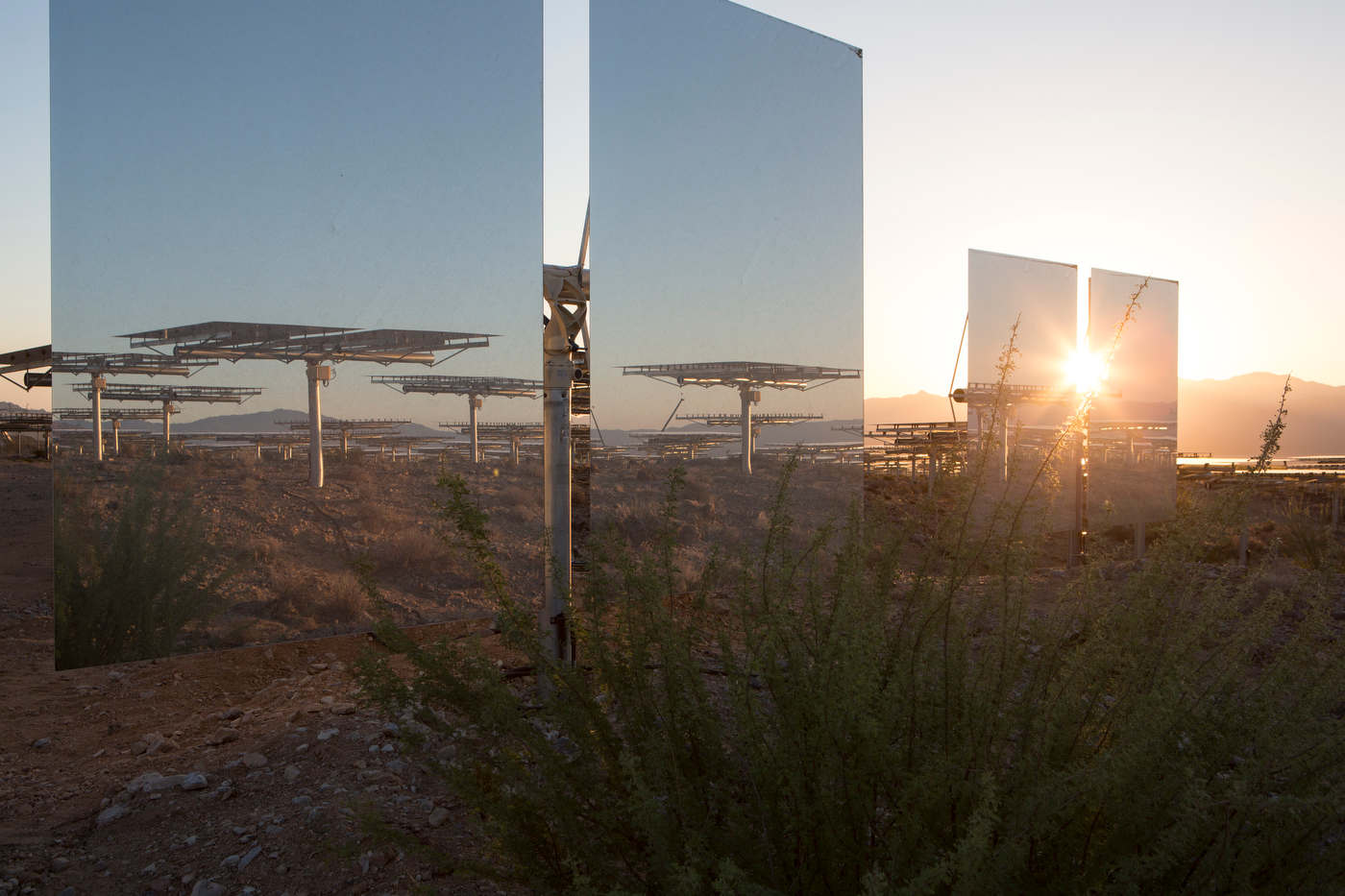 The rising sun peaks through two of Ivanpah's 174,000 mirrors.