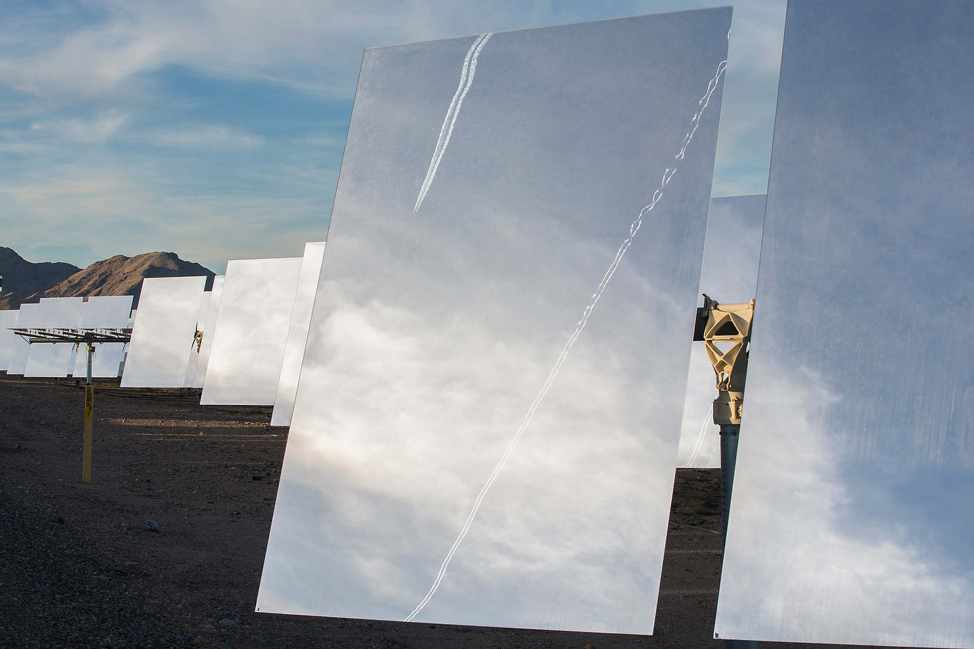 A passing jet's steam trail reflects in one of Ivanpah's 174,000 mirrors.