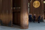 CENTRAL TOKYO, JAPAN - MARCH 18 2017: Visitors walk by a massive wooden door at the entance of the Yasukuni Shrine. The Yasukuni Shrine is a Shinto shrine in central Tokyo that commemorates Japan's war dead. The shrine was founded in 1869 with the purpose of enshrining those who have died in war for their country. The spirits of about 2.5 million people, who died in the conflicts accompanying the Meiji Restoration, in the Satsuma Rebellion, the First Sino-Japanese War, the Russo-Japanese War, the First World War, the Manchurian Incident, the Second Sino-Japanese War and the Pacific War, are enshrined at Yasukuni Shrine in form of written records, which note name, origin and date and place of death of everyone enshrined. A political controversy surrounds Yasukuni Shrine because since 1978, fourteen class A war criminals have been among the 2.5 million people enshrined at Yasukuni. Furthermore, the official visits by several Japanese prime ministers and cabinet members to the shrine since 1975 have been causing concerns regarding a violation of the principle of separation of church and state. Next to the shrine buildings stands the Yushukan, a large museum that commemorates Japan's wars from a conservative Japanese perspective with detailed information in English. Around the shrine grounds stand hundreds of cherry trees including Tokyo's representative cherry tree that is used by the meteorological agency to pronounce the official opening of the blossoms in the city (photo Gilles Mingasson).