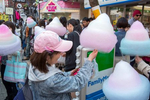 SHIBUYA-KU, TOKYO, JAPAN - MARCH 19 2017: Teenagers enjoy cotton candy on Takeshita-Dori, a shopping alley for teens, lined with small fashion stores and crepe stands. Takeshita Dori stands as a symbol of Tokyo's street cultures. Along this narrow sloping street (which runs from Harajuku station to Meiji Dori) you'll find stalls selling photos of fresh-faced 'idols' to star-struck schoolgirls, while the hip-hop boutique next door pumps out gangster rap. Shops specialising in 'Gothic Lolita' nurse and maid uniforms stand next to those selling retro-punk fashions and Beatles bootlegs. The shops on this street are often a bellwether for broader fads, and some are known as {quote}antenna shops,{quote} which manufacturers seed with prototypes for test-marketing (photo Gilles Mingasson).