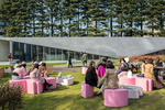 TOKYO, JAPAN -APRIL 2017: Office workers enjoy a lunch break in Roppongi's Midtown Garden near the Design Sight museum created by architect Tadao Ando and fashion designer Issey Miyake. {quote}The idea was to create not only a museum that shows exhibits,{quote} says Ando, {quote}but also a place for researching the potentiality of design as an element that enriches our daily life, a place that fosters the public's interest in design by arousing in them different sights and perspectives on how we can view the world and the objects surrounding us.{quote} The building, designed by Ando, is on the edge of a park area, and features 1,700 square meters (18,300 sq ft) of floor space, including two galleries and an attached cafe run by chef and restaurateur Takamasa Uetake. The split-level concrete structure includes a hand-sanded steel roof (whose design was inspired by Issey Miyake's A-POC ({quote}A Piece of Cloth{quote}) concept) and 14-meter (46 ft) long glass panels (photo Gilles Mingasson).