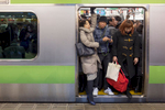 SHINJUKU STATION, TOKYO, JAPAN -FEBRUARY 01 2017: Morning commuters pack themselves into a train on one of the 36 platforms at Shinjuku Station, the world's busiest transit hub, handling over 3.6 million passengers a day, or approximately 1.26 billions each year. Japanese organisation and civility help make the process a relatively smooth, if somewhat claustrophobic, experience, as commuters pack each train to the maximum, helped by attendants once known as pushers (they used to literally push people inside the train), who help keep things running smoothly. With an urban area 38 million and the largest metropolitan economy in the world, Tokyo depends on the most extensive urban railway network in the world to move people around the city (photo Gilles Mingasson for National Geographic Books).
