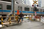 SHINJUKU, TOKYO: A man on a bicycle waits at a train crossing (photo Gilles Mingasson).