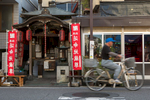 YANAKA, TOKYO: FA bicycle rides past a neighborhood shrine in Yanaka. Yanaka is one of the few districts in Tokyo where the shitamachi atmosphere, an old town ambience reminiscent of Tokyo from past decades, still survives. Different trades line the streets, starkly contrasting each other: the butcher's beside the barber's, the confectionery beside the watch dealer. Prices are relatively cheap as well; little snacks and finger food sold from below 50 yen can be found in some stalls. Yanaka remains a residential district where many locals live, and through Yanaka Ginza, visitors can observe the ongoing daily activities and trades carried out in the district market (photo Gilles Mingasson).