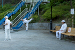 SINJUKU-KU, TOKYO -MAY 2017: Locals residents stretch before an early morning session of rajio taisō in Edogawa park. Rajio taisō was introduced to Japan in 1928 as a commemoration of the coronation of Emperor Hirohito. The idea for radio broadcast calisthenics came from the US, where during the 1920s the Metropolitan Life Insurance Co. sponsored 15-minute radio calisthenics in major cities in the US. Visiting employees of the Japanese postal insurance division brought samples of the exercises from the US back to Japan. The exercises were widely used to improve the health of Japanese soldiers both at home and abroad during the 1930s and 1940s. After Japan's defeat in 1945, the broadcasts were banned by the occupying powers as being too militaristic in nature. After several rewrites to the exercise routine, it was reintroduced by NHK radio in 1951 with the support of the education ministry, health ministry, the Japan Gymnastic Association and the Japan Recreation Association (photo Gilles Mingasson).