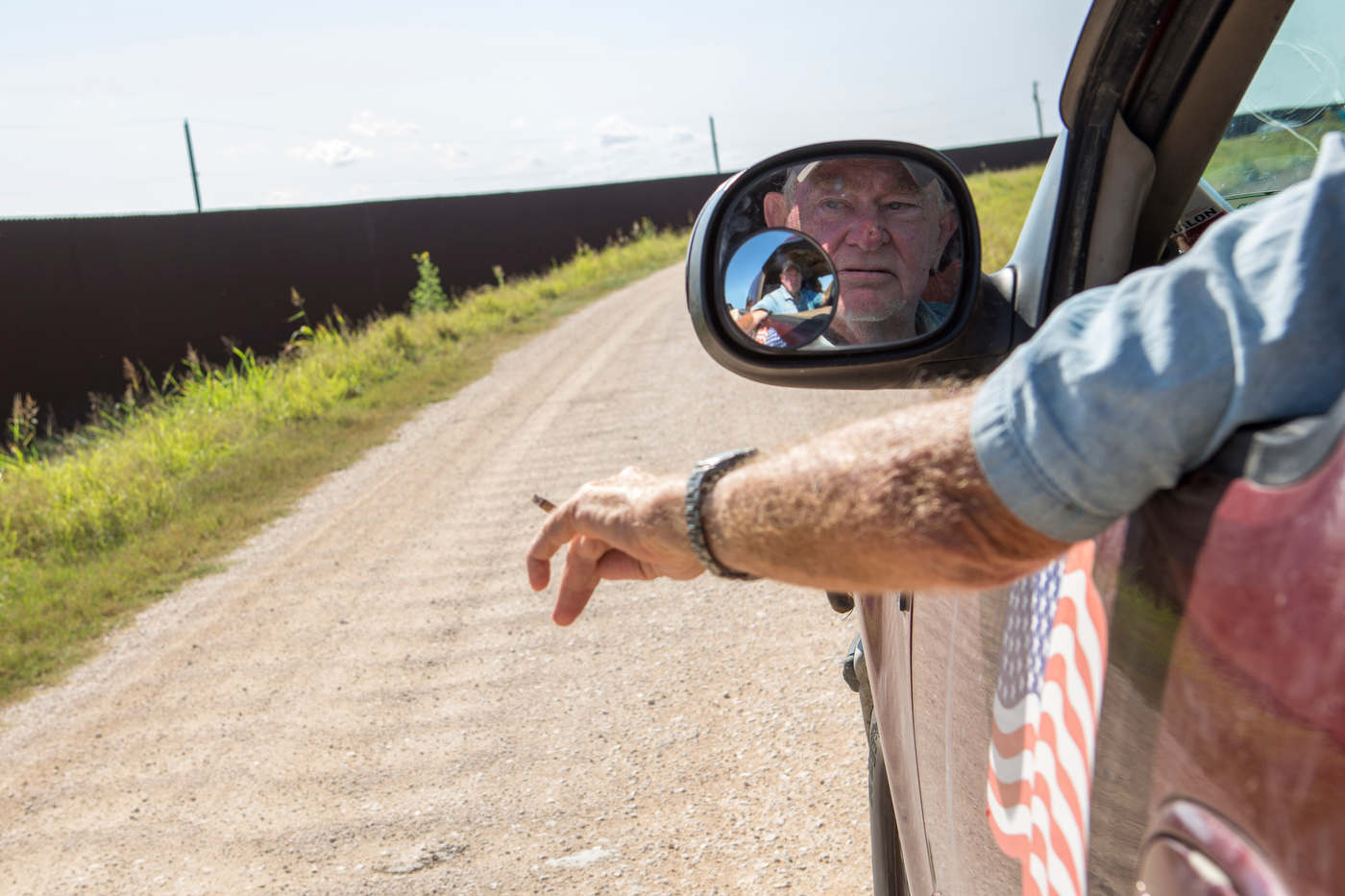 Rusty Monsees, an anti-immigration activist whose land is cut in half by the border wall, drives on his property between the fence and the Rio Grande, a no man's land.