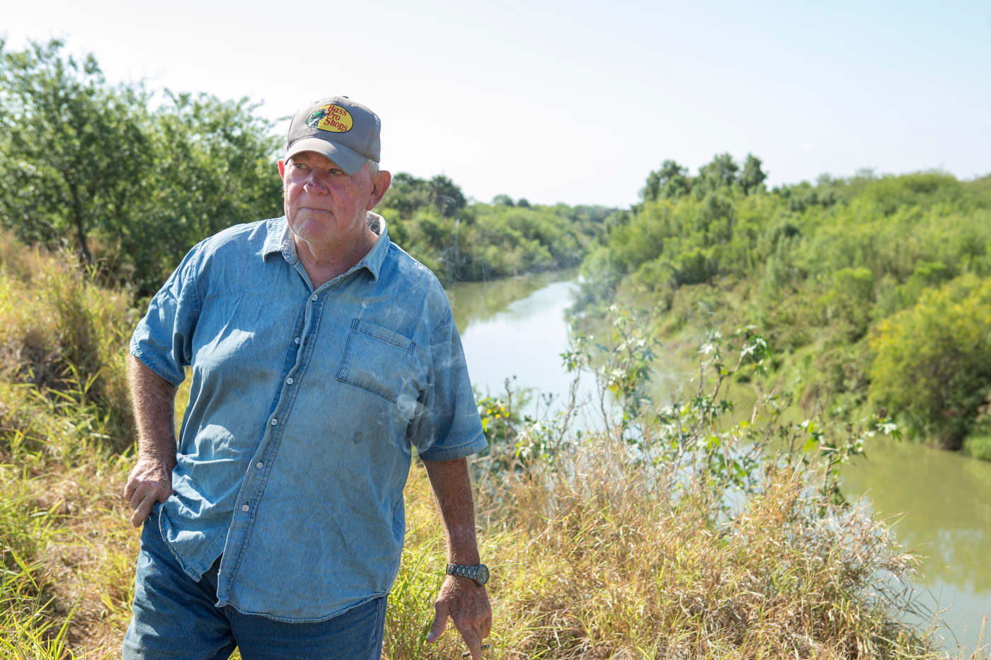 Rusty Monsees, an anti-immigration activist whose land is cut in half by the border wall, stands on his property next to the Rio Grande, in the no man's land between the river and the fence.