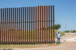 Rusty Monsees, an anti-immigration activist whose land is cut in half by the border wall, stands near the fence on his property.