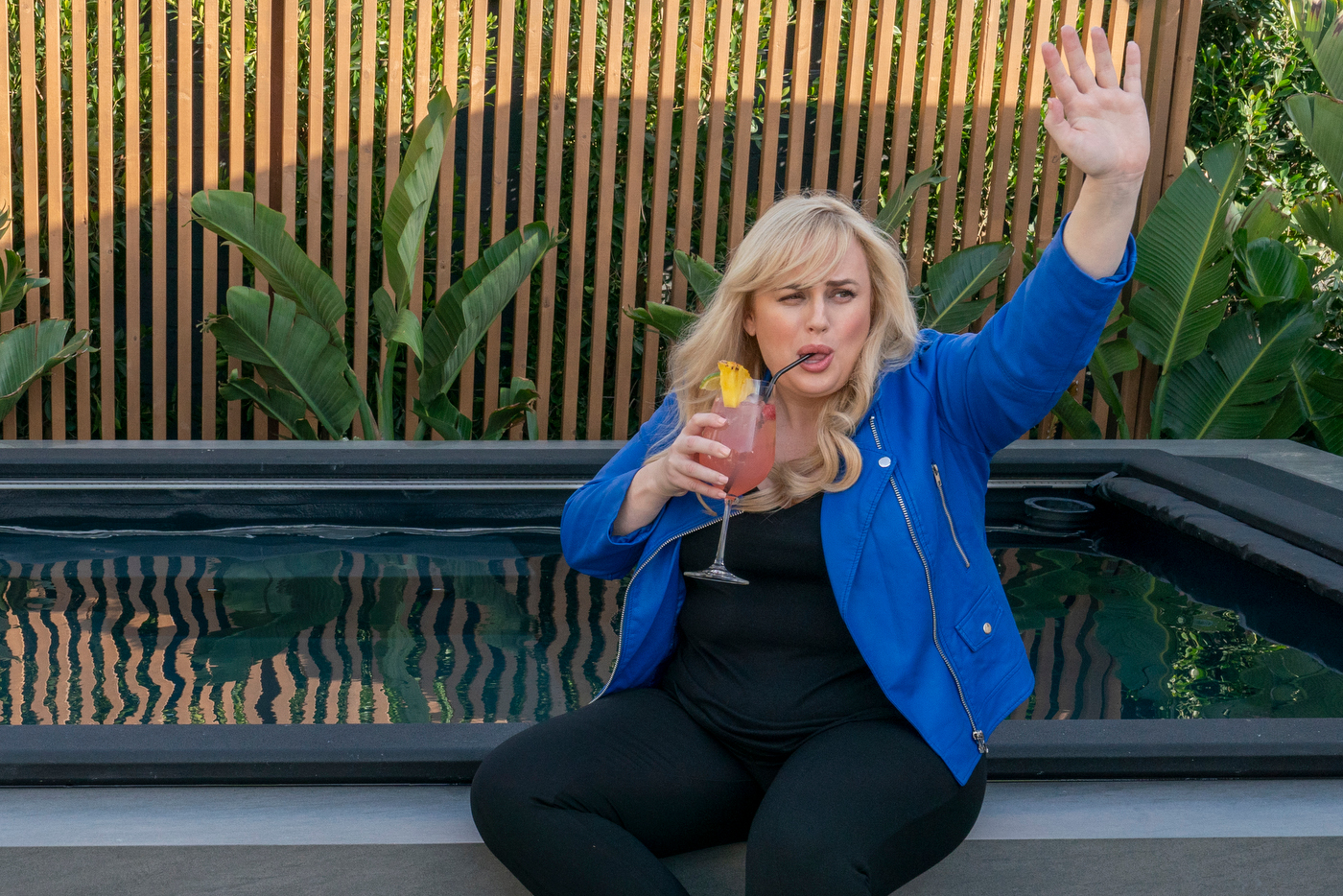 As seen on Celebrity IOU, actress Rebel Wilson waves goodbye to Drew and Jonathan Scott after revealing the new outdoor space that she renovated for her longtime hairdresser and friend Nicole with the Scott brothers.
