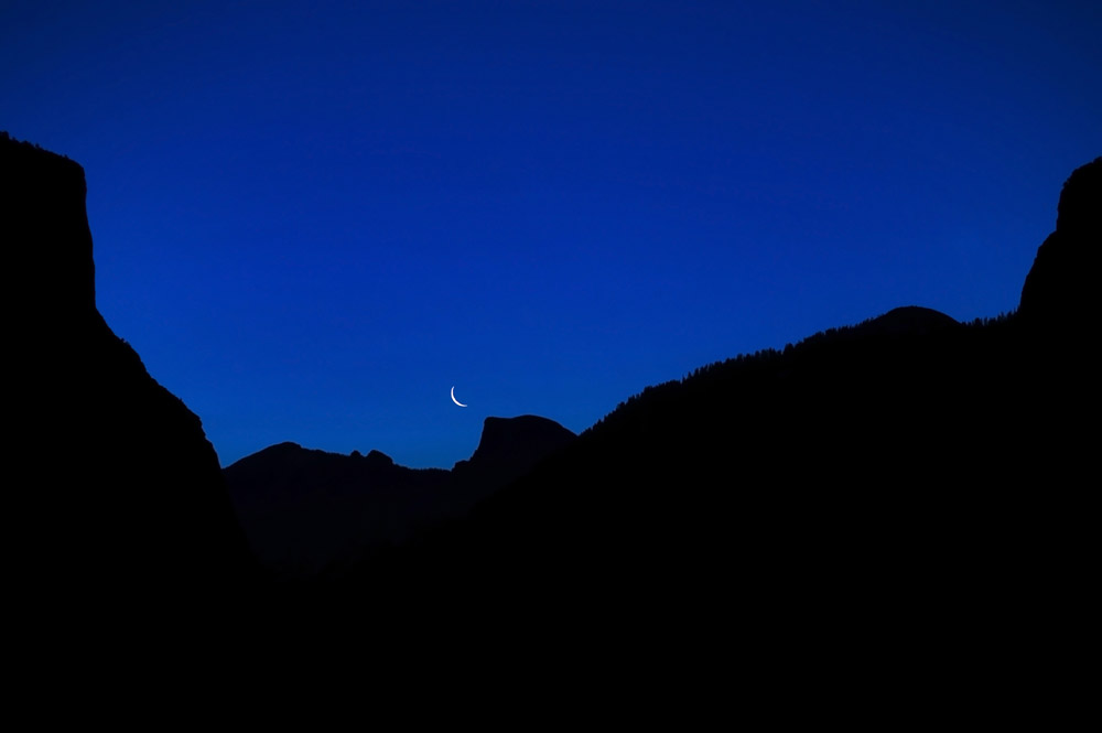 Crescent moon rises above Half Dome.  Picture is bordered by El Capitan on the left and Cathederal Rocks on the right.  This image was shot early morning before sunrise which occured 30 minutes later.  A once in a life time experience as the conditions were perfect.