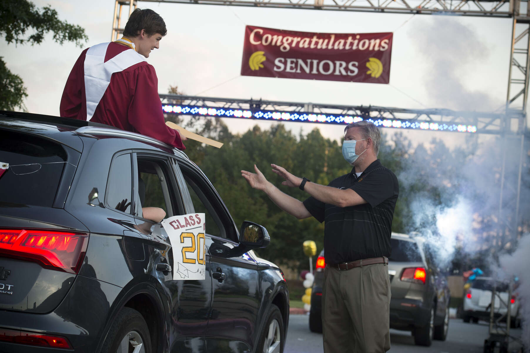 A senior at Lassiter High School north  of Atlanta, receives his diploma from masked Principal Dr. Chris Richie, in a parade of hundreds of students around the school grounds. .The parade used social distancing measures in personal cars instead of the more typical auditorium stage walk in recognition of the threat infecting others with Covid-19  virus.