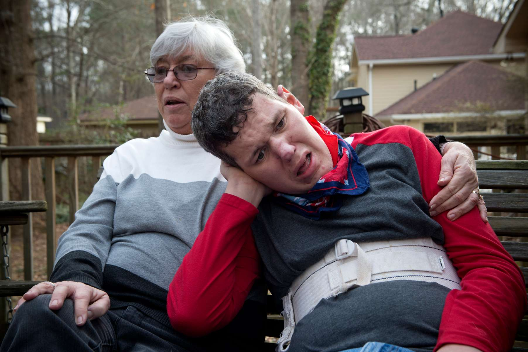 "Sheila McBroom comforts her disabled son Tim as they sit on the family deck.   McBroom and her husband Mike  often lie awake at night, filled with anxiety about Tim's future. Tim, 36, who is non-verbal and experiences severe autism, has seizures and behavioral issues. McBroom and his wife are doing their best to provide their son with a safe and secure environment in their Jonesboro home, with daily help from Medicaid waiver-funded support staff. But proposed cutbacks to those Medicaid-funded services turn their son's life upside down. Georgia's disability officials are currently wrestling with likely budget cuts that will dramatically impact their son, and 187 others in the state with profound intellectual disabilities who need extensive daily support to remain at home.The state's proposed cutbacks affect 187 individuals like Tim who need more than 16 hours a day of support that allows them to remain at home, integrate into their communities, and enjoy some degree of independence, Mike McBroom explained.  ""Under proposed changes to the waiver, Tim will no longer qualify for the person-centered care he needs to remain here,"" he said.  ""State officials said they have identified the needed numbers of beds in various locations around the state -- and all of them are in group homes."""