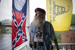A group of angry demonstrators gathered outside Dent Myers' Civil War Relic and Antique Shop Friday to protest the 89-year-old owner's obsession with what they see as a racist and bigoted past. Pictured: Dent Myers on top floor of building that houses his relic shop, keeping an eye on gathering protesters.