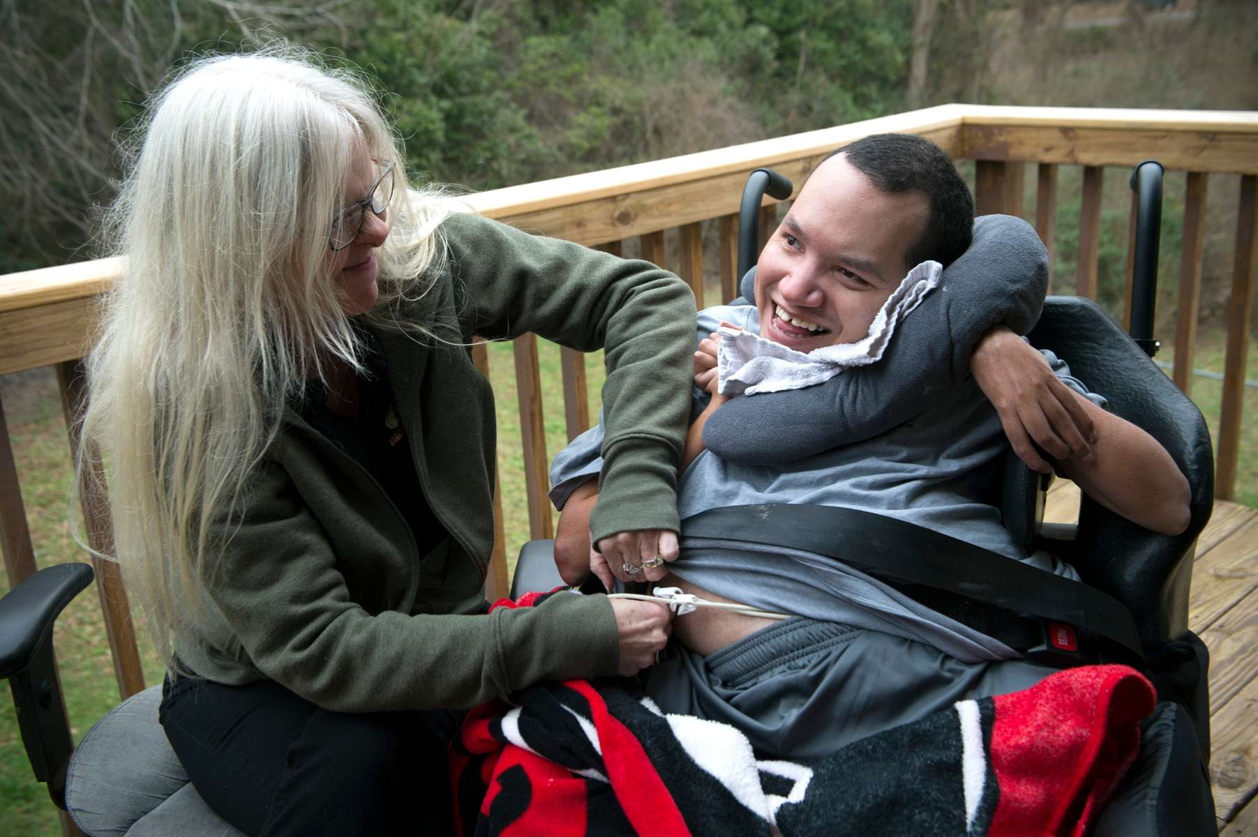 "LISA ARCHIBALD has been caring for her profoundly disabled brother John David in her home for more than 20 years. John David, 36, is non-verbal, quadriplegic, and medically fragile because of cerebral palsy, polymicrogyria, and dysplasia. He lives in Archibald's home and requires 24-hour care. He has seizures, restrictive lung disease and silent aspiration into his lungs, which requires constant supervision to prevent choking.Archibald has been able to care for her brother in her home with the help of a patchwork of support staff, funded by a Medicaid waiver for daily in-home care. ""He really requires 24-7, two-to-one care, but we've been making do with the staffing hours we've had for many years,"" explained Archibald, 53, who provides much of his hands-on care herself. She assumed responsibility for his care since their mother died 23 years ago. She removed walls in her living room to accommodate his bed and medical equipment. His care is center-stage in her life.But that care is now uncertain, and Archibald faces a grim decision.If proposed caps for support for Georgia's medically-fragile residents become reality in two months, ""Families will have to make one of the most gut-wrenching decisions of our lives:  to choose between quitting our jobs, losing the ability to support ourselves and other family members in order to care for our person, or placing our medically-fragile family member in a group or nursing home,"" she said.""My brother was in a group home for several years, and nearly died. To place him back into another group home would be a death sentence. He would not survive. John David loves being at home and being a part of our community,"" she said. ""He knows he's loved.""Pictured: Lisa Archibald adjusts tube that constantly feeds into to her brother's stomach."