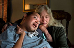 """Lisa Archibald has been caring for her non-verbal and profoundly disabled brother John David in her home for more than 20 years. With multiple physical and developmental disabilities, he requires 24-7 care. Proposed cuts in Georgia's Medicaid disability budgets may force relocation to a group or nursing home, a move Archibald considers a 'death sentence' because of his extensive care requirements, high turnover and inadequate staff training. """"We tried a group home years ago, and he nearly died,"""" she said. """"I won't do that to him again, though that is what the state is advocating."""" John David requires 24/7 care with 2:1 staffing, including one LPN or RN, she said. The cuts would require Archibald to increase the time she cares for him to 20 hours daily, leaving little time to sleep or work, she said.  Georgia currently has 187  medically fragile residents who would be impacted by the state's proposed budget cuts."""