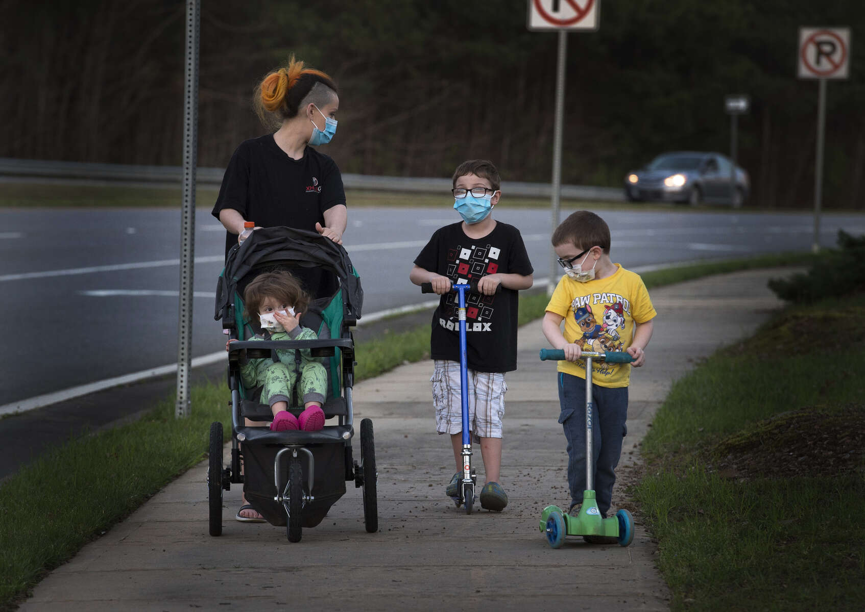 Stephanie Barker, 32, walks with her children along a parkway on a Spring evening, all wearing face masks as protection auto guard against the COVID-19 virus pandemic.