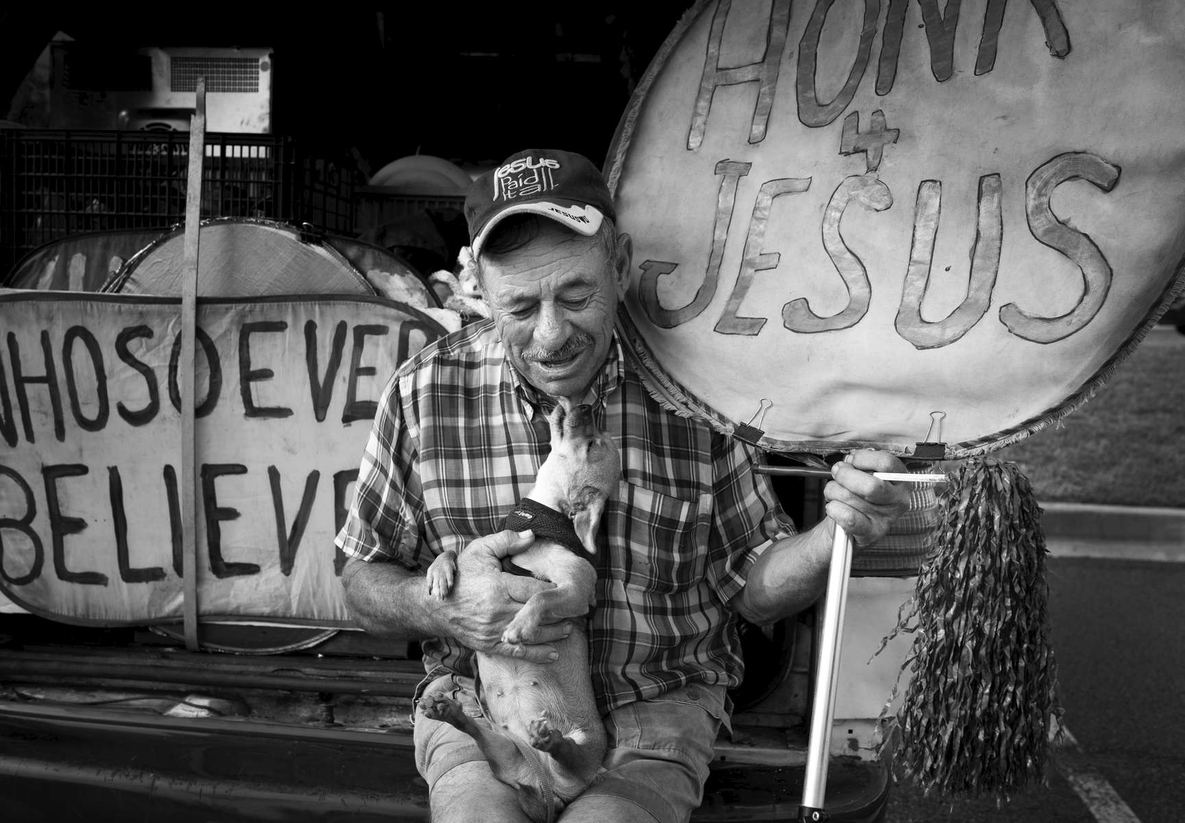 "George Kranock, a self-described traveling evangelist, kisses his dog Tulip at the rear of his aging Ford van during a break from his street evangelism in Kennesaw, Ga.  Kranock, 74, originally from New Jersey, uses his meager Social Security benefits to pay for his gas and lives on day-old sandwiches from grocery stores as they travel throughout the South, standing along busy highways to hold his 'Honk 4 Jesus' sign.  He seeks no donations or financial support. ""I have a special love for Georgia. People here really do love the Lord,"" he said. ""This is my calling, to let people know Jesus loves them."""