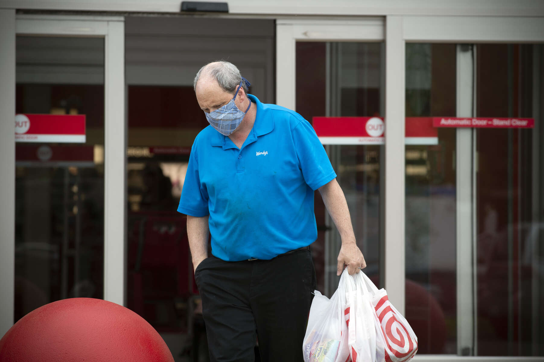 A shopper wearing a hand-crafted face mask as protection against the Covid-19 virus exists a grocery store with just a few items.