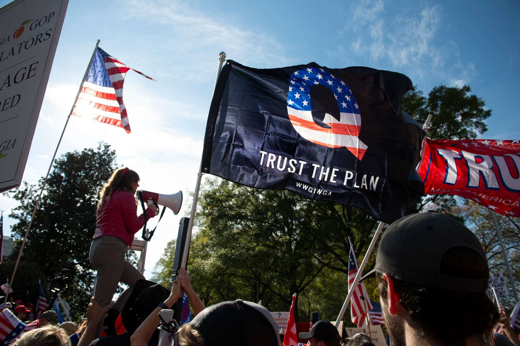 Hundreds of Georgia Republicans gather outside Capitol in Atlanta at rally to show support for President Trump.Pictured: QAnon flag flies at rally
