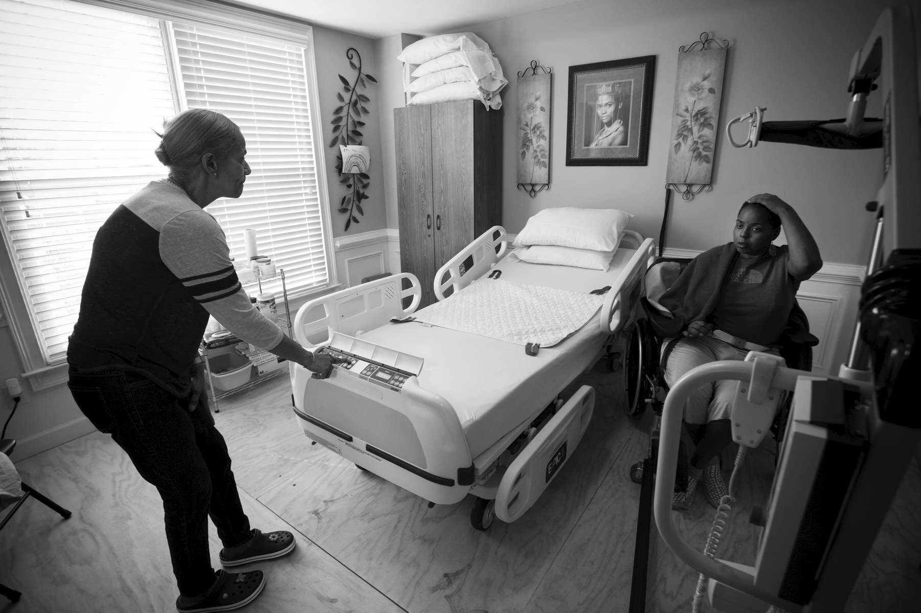 Erika Jones, 32,  is on the slow path to recovery from a brain tumor that left her paralyzed and unable to speak more than a few words. Her mother Joyce Jones insisted she be moved back into her family's home rather than a nursing facility. {quote}I am committed to caring for my baby until the day I die,{quote} Joyce explained. {quote}She wouldn't get that love in a nursing home.{quote} Pictured: Joyce Jones chats with Erika in what was once family dining room, now converted to Erika's room on the ground floor.