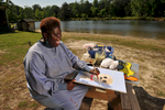 """Decatur, GA – Ten years after the U.S. Supreme Court's landmark """"Olmstead"""" decision made it possible for mentally disabled persons to live within their communities rather than state mental hospitals, 41-year-old LOIS CURTIS is all smiles, loving her life beyond locked doors and high fences.A self-taught artist, Curtis spent much of her life in various mental institutions. Following denial of numerous requests to live in her community, she initiated a lawsuit against the state of Georgia. In July, 1999 the U.S. Supreme Court ruled that 'unnecessary institutionalization' amounted to segregation and violated individuals' civil rights. Her case established a national mandate to free tens of thousands of people with disabilities from institutionalization. Today, Ms. Curtis receives community-based support and enjoys life outside the confines of institutional living. Her artistic talent and passion for creativity have motivated her to make art and advocacy her life's work. Her artwork, typically done in pastels and acrylics, are heartfelt, bold expressions of how deeply she values personal relationships.  They are mainly portraits, capturing intense emotions with simple lines and bold colors. """"I feel good about myself. Sometimes I put my mind on the earth and go to the future where my art pictures are on the wall. People would love to see my pretty art pictures because they will take them to heaven and hug them forever,"""" says Ms. Curtis. Her supporters have arranged for dozens of art shows in the Atlanta area, and she is now an invited speaker to conferences nationwide. Pictured: Lois paints wildlife at Pine Lake, an artist community near Atlanta where Lois dreams of living."""