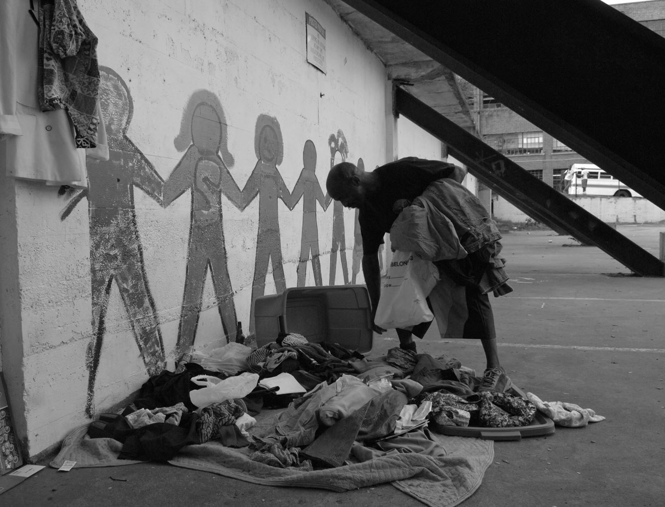 A homeless man sifts through discarded clothing near a homeless shelter, looking for something that might fit.