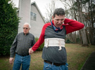 """Mike McBroom escorts his disabled son for a walk outside the family home. Mike and his wife Sheila often lie awake at night, filled with anxiety about Tim's future. Tim, 36, who is non-verbal and experiences severe autism, has seizures and behavioral issues. McBroom and his wife are doing their best to provide their son with a safe and secure environment in their Jonesboro home, with daily help from Medicaid waiver-funded support staff. But proposed cutbacks to those Medicaid-funded services turn their son's life upside down. Georgia's disability officials are currently wrestling with likely budget cuts that will dramatically impact their son, and 187 others in the state with profound intellectual disabilities who need extensive daily support to remain at home.The state's proposed cutbacks affect 187 individuals like Tim who need more than 16 hours a day of support that allows them to remain at home, integrate into their communities, and enjoy some degree of independence, Mike McBroom explained.  """"Under proposed changes to the waiver, Tim will no longer qualify for the person-centered care he needs to remain here,"""" he said.  """"State officials said they have identified the needed numbers of beds in various locations around the state -- and all of them are in group homes."""""""