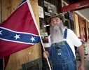 LAMARR MAYES, 64, from Fairmount, GA, holds his personal Confederate Battle Flag replica outside Dent Myers' Civil War Surplus store, where regular visitors often meet to share their views on society with others who appreciate ways of the 'Old South.'