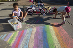 Morgan Johnson, 7, and her 3-year-old sister Nora entertain themselves making chalk drawings on their family's driveway. Now under 'shelter in place' orders by city government order, the girls' parents spend much of their days supervising and suggesting fun activities to keep them engaged and upbeat.