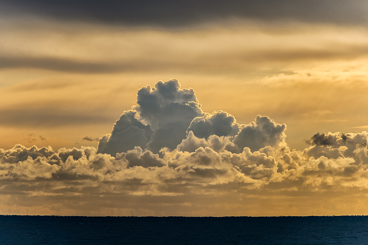 Gorgeous photogrphic image of cumulus clouds over the sea at sunset with strong yellow tones.  Fine Art Print & Canvas Gellery Wrap for Sale.