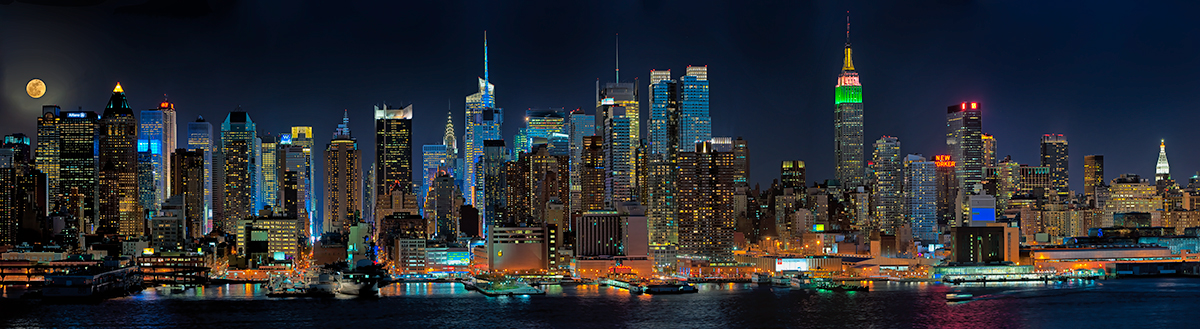 Night panoramic photograph of the Manhattan Skyline with a full moon rising available as a fine art print, canvas gallery wrap or for licensed use