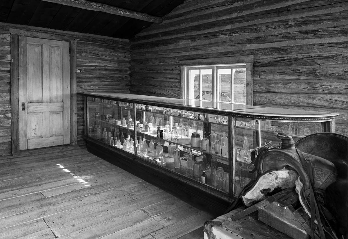 Black and White Photograph of Genuine old log cabins and businesses from the Wild West Moved to The Museum and RestoredImage No: 17-016997-BW  Click HERE to Add to Cart