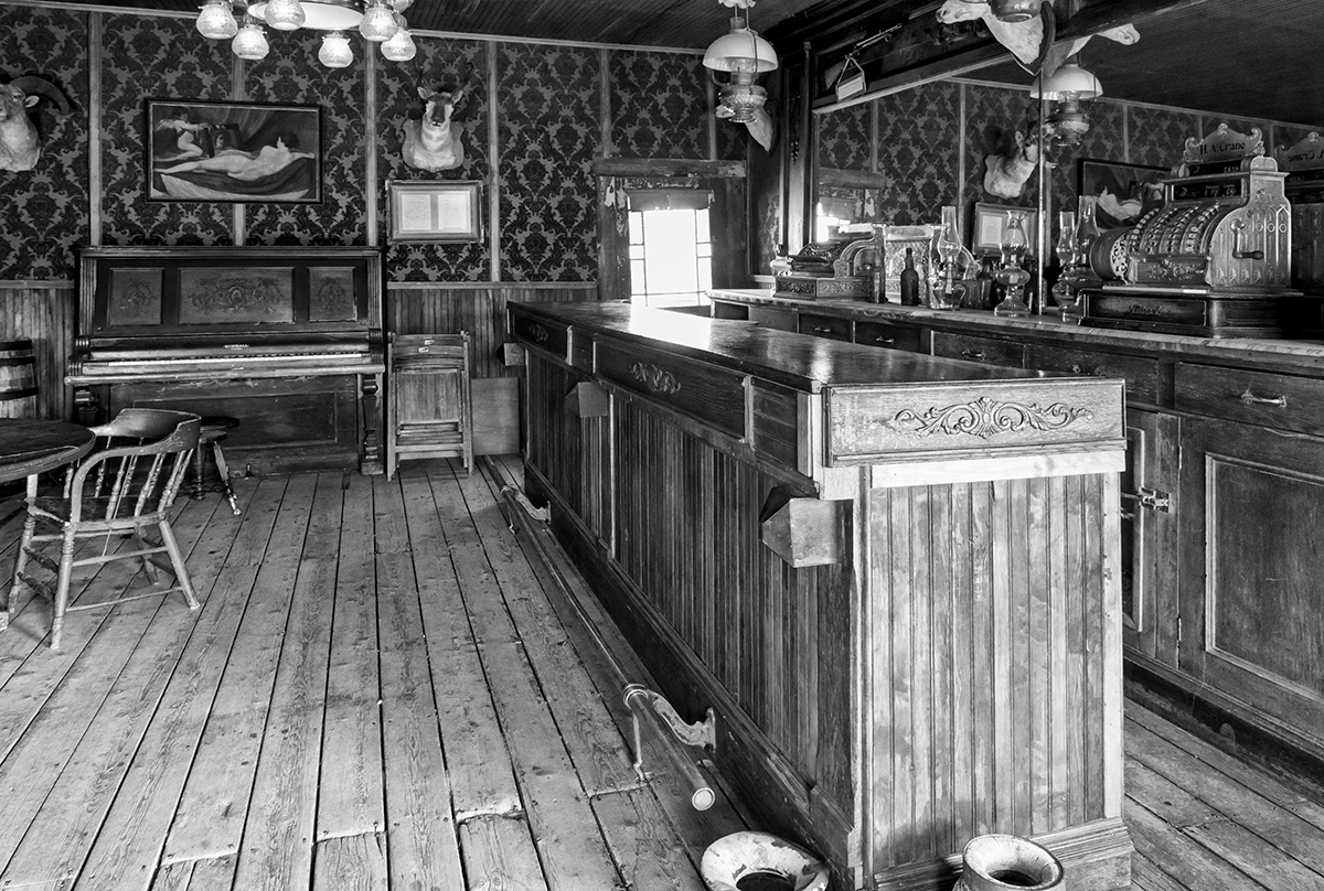 Black and White Photograph of Genuine old log cabins and businesses from the Wild West Moved to The Museum and RestoredImage No: 17-017102-BW  Click HERE to Add to Cart