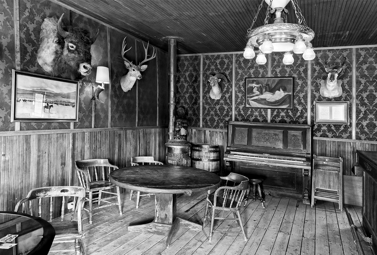 Black and White Photograph of Genuine old log cabins and businesses from the Wild West Moved to The Museum and RestoredImage No: 17-017105-BW  Click HERE to Add to Cart