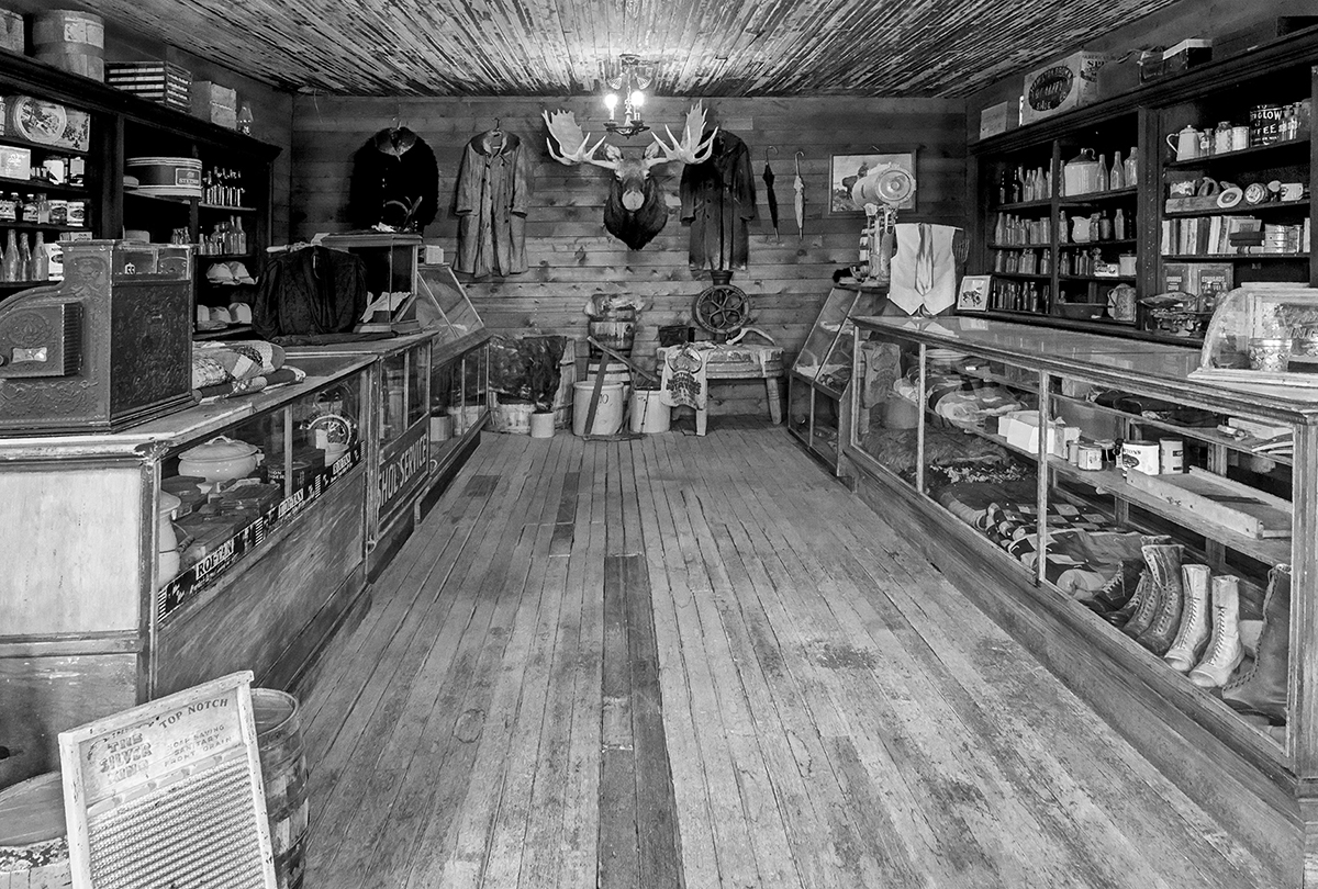Black and White Photograph of Genuine old log cabins and businesses from the Wild West Moved to The Museum and RestoredImage No: 17-016948-BW  Click HERE to Add to Cart