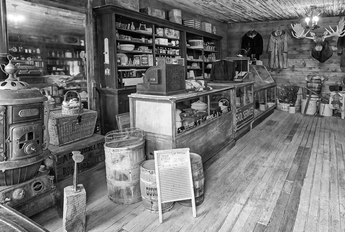 Black and White Photograph of Genuine old log cabins and businesses from the Wild West Moved to The Museum and RestoredImage No: 17-016955-BW  Click HERE to Add to Cart