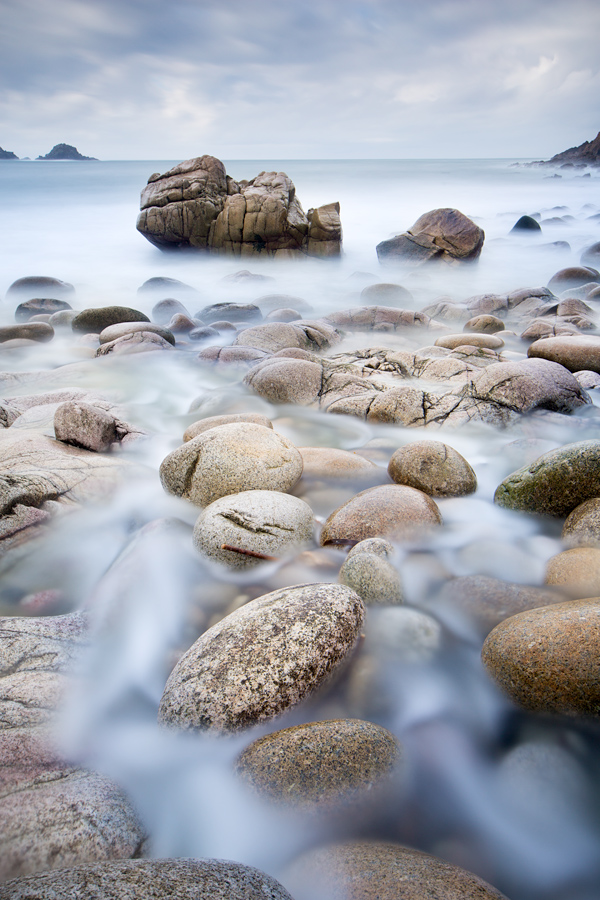 I stood in the fast-flowing stream where fresh water from the hills flowed down into the sea and in the mid-ground laid a huge boulder. Seeing that from a distance, I decided to explore the area and headed in that direction. The ample rounded rocks provided a nice foreground and separation of the water flow. A LEE Big Stopper 10 stop ND filter slowed the shutter speed to give the water a cliche silky look. Well it does look quite alright here. Canon 5D Mark III, 24 TSE II, Processed in Photoshop CS6.